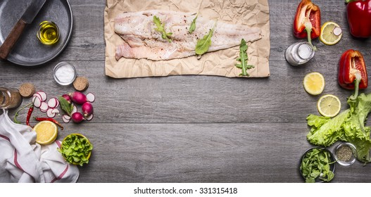 Ingredients for cooking raw cod on paper with herbs knife lemon oil pan Radisson napkin and lettuce with pepper on rustic wooden background top view border space for text banner for the web site