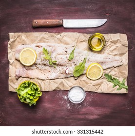 Ingredients for cooking raw cod on peper knife lemon arugula lettuce salt oil on rustic wooden background top view close up