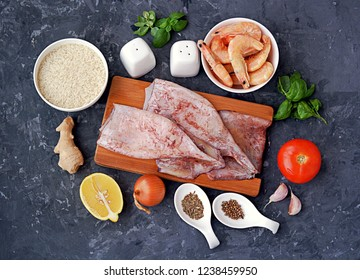 Ingredients for cooking rice with shrimps and squid: dry rice, squid, shrimp, half a lemon, tomato, ginger, onion, garlic, salt, fresh basil, spices. Top view.