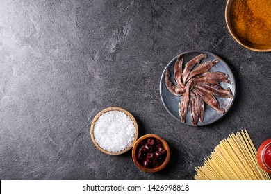 Ingredients for cooking spaghetti anchovy pasta: salt in wooden bowl, olives, anchovies and tomato sauce over grey texture background. Top view, flat lay, copy space