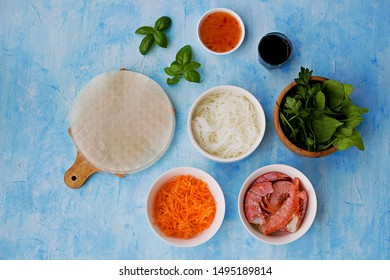 Ingredients for cooking spring rolls: sheets of rice paper, rice noodles, grated carrots, shrimps, salad mixture, soy sauce, chili sauce, basil. Top view. Vietnamese cuisine.