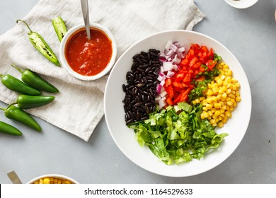 Ingredients for the cooking of taco salad on gray concrete background, top view