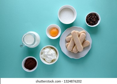 Ingredients for cooking tiramisu: sponge fingers cookies (Savoiardi, Ladyfinger, biscuit), mascarpone, cream, sugar, cocoa, coffee and egg on blue background. Top view. Flat lay