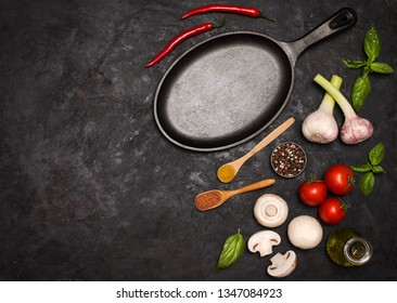 Ingredients for cooking  with tomatoes, garlic ,mushroom,  on a dark background. Mushrooms, fresh garlic, tomatoes, spices, basil, near the cast iron frying pan.