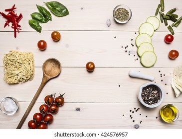 Ingredients for cooking vegetarian food, cherry tomatoes, basil, zucchini, mortar pepper, oil, wooden spoon, laid out on a white wooden table, top view