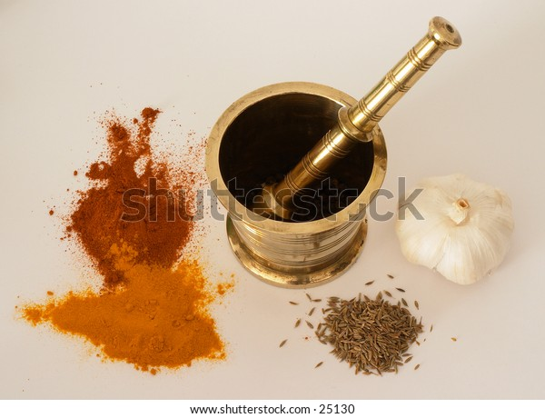 Ingredients for curry, chili, cumin, garlic, and turmeric, with a pestle and mortar.