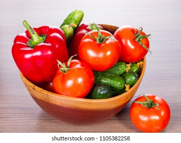 Ingredients for Dietary Salad. on a table in wooden plate cucumbers, tomatoes and pepper. healthy food fresh vegetables.