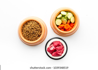 Ingredients for dry pet food. Meat and vegetables zucchini and carrot on white backgroud top view copy space