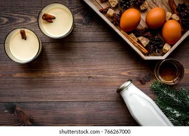 Ingredients for eggnog. Eggs, milk, cinnamon, whiskey on dark wooden background top view copyspace
