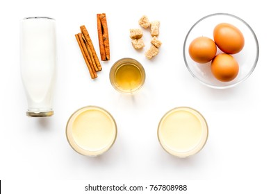 Ingredients for eggnog. Eggs, milk, cinnamon, whiskey on white background top view