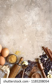 Ingredients for festive baking : flour, brown sugar, eggs, chocolate slices and drops, cocoa, butter and cinnamon on a beige slate, stone or concrete background.Top view with copy space.