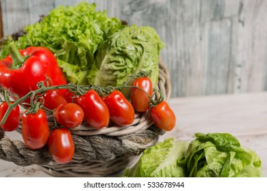 Ingredients for fresh spring healthy green salad. Green fresh roma lettuce salad leaves and roma mini tomatoes - healthy low calorie food