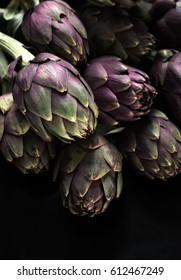 Ingredients. Fresh textured artichokes on a dark backgroun