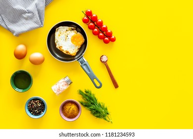 Ingredients for fried eggs with vegetables. Ready eggs in a frying pan near cherry tomatoes, greenery, spices, raw eggs on yellow background top view space for text