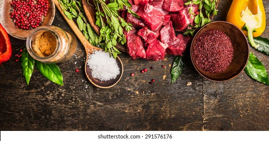 Ingredients for goulash or stew cooking: raw meat, herbs,spices,vegetables and spoon of salt on rustic wooden background, top view. Banner for website.