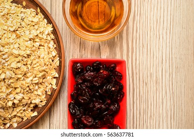 Ingredients for granola on a wooden background, healthy breakfast idea, vegan, dieting and detox concept with copy space. Oatmeal, dried cranberries and honey