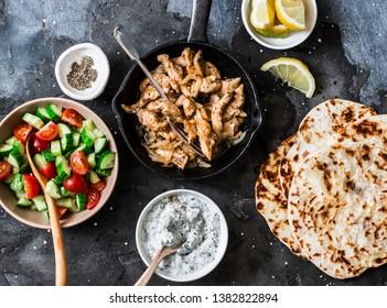 Ingredients for greek chicken gyros - fried chicken, tomato cucumber salad, tzatziki sauce and flatbread on a dark background, top view. Flat lay