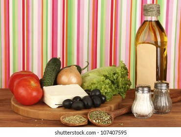 Ingredients for a Greek salad on bright striped background close-up