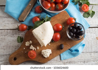ingredients for greek salad on a wooden board