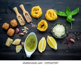 The ingredients for green pesto sauce on dark wooden background.