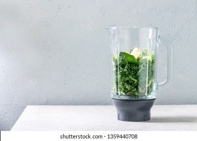 Ingredients for green spinach kale apple smoothie in glass blender on white marble table. Healthy organic eating.
