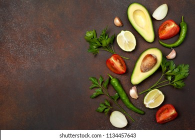 Ingredients for guacamole: avocado, lime, tomato, onion and spices on a brown background. view from above. copy space