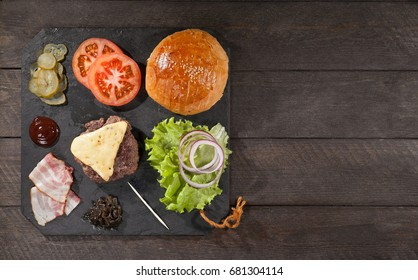 Ingredients for a hamburger on a slate board.top view.