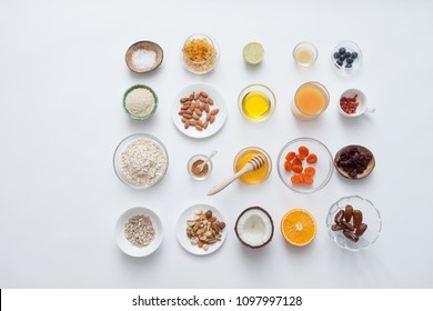 Ingredients for a healthy breakfast - granola, honey, nuts, berries, fruits, on white, top view.