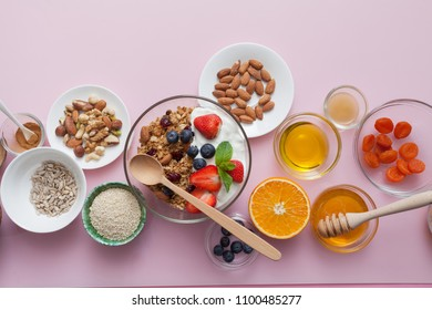 Ingredients for a healthy breakfast - granola, honey, nuts, berries, fruits, on pink background, top view.