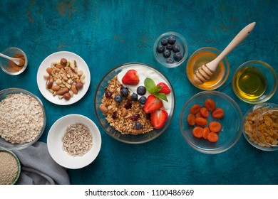 Ingredients for a healthy breakfast - granola, honey, nuts, berries, fruits, on blue background, top view.