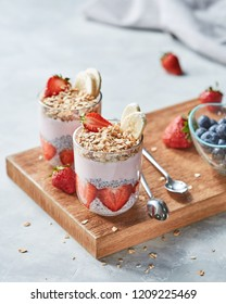 Ingredients for healthy breakfast - homemade granola, halves of strawberries, chia seeds, blueberries and yogurt in a glasses with a spoons on a wooden board on a gray concrete background.