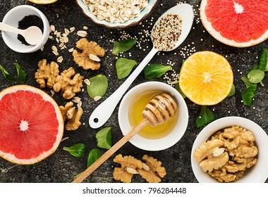 Ingredients for a healthy breakfast meal on a dark background red ruby bloody grapefruit, oat flakes, kinoa, green leave, walnut, flower honey, orange, black sesame. Top view. Concept  vegetarian food