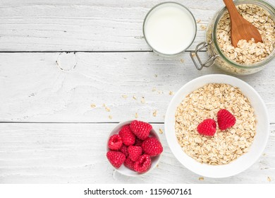 Ingredients for healthy breakfast - miilk, raspberries and oat muesli on white wooden table. top view with copy space