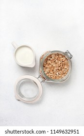 ingredients for a healthy breakfast: muesli and milk on a white concrete background. view from above