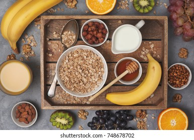 Ingredients for a healthy breakfast: muesli, milk, honey, fruits and nuts in a wooden tray on a gray concrete background. view from above