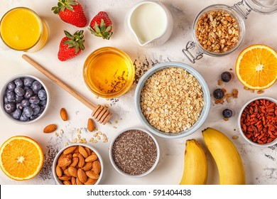 Ingredients for a healthy breakfast -  oatmeal, granola, honey, nuts, berries, fruits, top view.