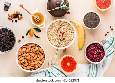 Ingredients for a healthy breakfast: oatmeal, honey, berries, fruits,berries, grapefruit, chia seeds, almonds, raisins, banana and herbal tea. The concept of natural organic food in season. Top view