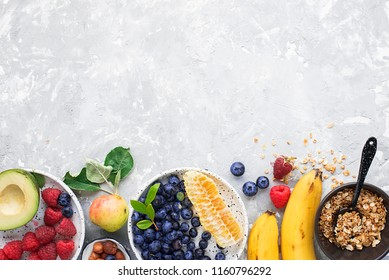 Ingredients of a healthy breakfast: raspberries, blueberries, oat flakes, granola, honey, nuts, banana, avocado kiwi on the background Top View