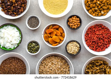Ingredients of healthy breakfast with superfood on table, seeds, fruits, cereal, nuts, almonds, goji berries, healthy food, flat lay, overhead