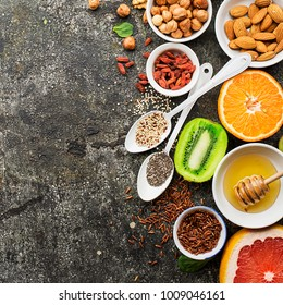 Ingredients of healthy dietary food breakfast pink grapefruit, orange, chia seeds, quinoa, green herbs, kiwi, wild rice, almonds, walnuts, hazelnuts on a gray background. Vegetarian friendly. Top View