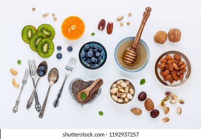 Ingredients for a healthy foods background, nuts, honey, berries, fruits, blueberry, orange, almonds, walnuts and chia seeds .The concept of healthy food set up on white wooden background. Flat lay.