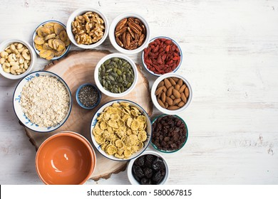 Ingredients for healthy granola: nuts, oats, cereals and dried fruits on the white wooden table, top view, selective focus, copy space