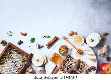 Ingredients for healthy hot drink. Lemon, ginger, mint, honey, apple and spices on grey concrete background. Copy space. Top view. Alternative medicine concept. Clean eating, detox.