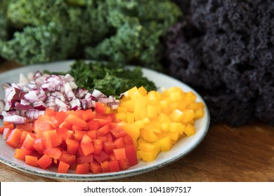 Ingredients for a healthy salad including bell peppers, onions, and kale.