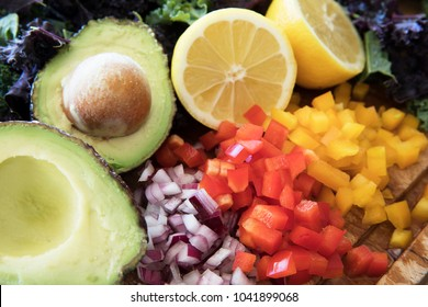 Ingredients for a healthy salad including bell peppers, onions, avocado, lemons, and kale.