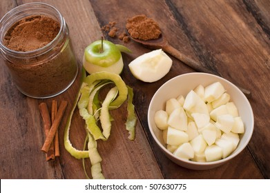 Ingredients for homemade apple sauce with peeled and diced fresh green cooking apples , stick cinnamon and aromatic ground spice for seasoning on a wooden table