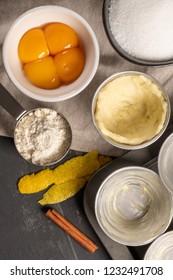 Ingredients for homemade baking portuguese egg tarts - flour, milk, water, egg, sugar, lemon, cinnamon, pastry and cake pan. Traditional portuguese dessert pastel de nata