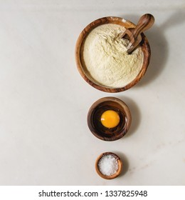 Ingredients for homemade italian pasta ravioli cooking semolina flour, egg yolk, sea salt in olive wood bowls over white marble background. Flat lay, space. Home baking concept. Square image