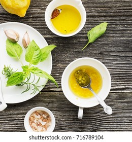 Ingredients for homemade lemon sauce vinaigrette dressing for salad with olive oil, salt, pepper, lemon, lemon zest, juice, garlic and herbs to taste. Top view on a wooden background