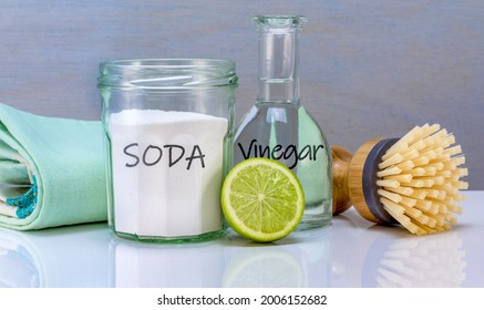 ingredients for homemade homemade natural eco cleaner with soda, vinegar and lime in recycled jars and bamboo scrubbing brush, sustainable living